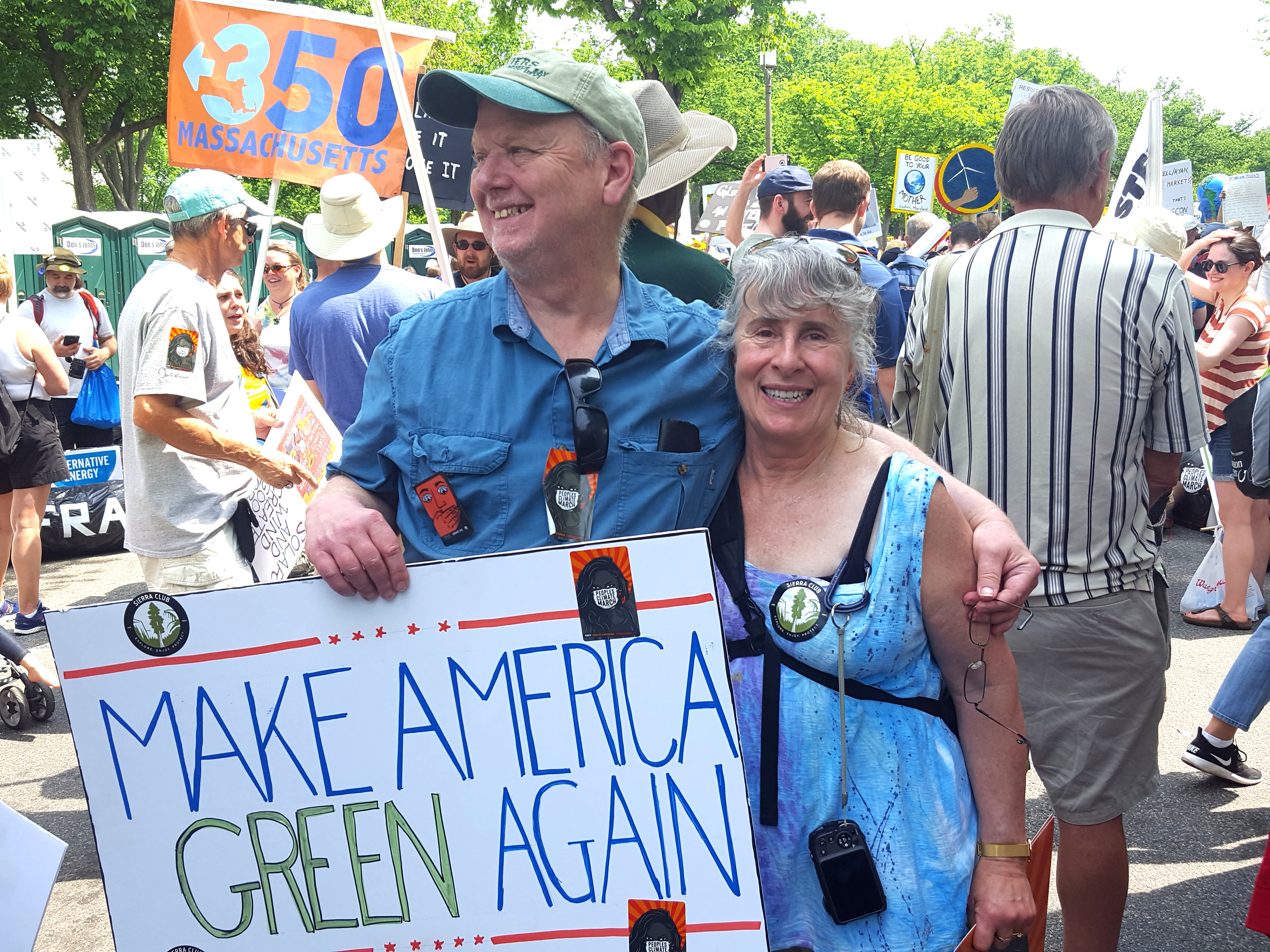 "Jesse at the 2017 Climate March in Washington, DC with his partner, Nancy Parks. Both are smiling and Jesse is holding a sign that says ""Make America Green Again."""